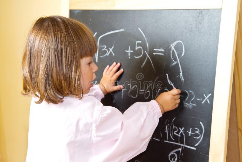 Il bambino disegna con gesso sulla lavagna immagini stock