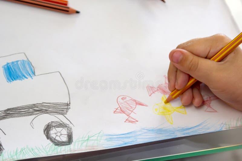 Il bambino disegna con le matite variopinte Il tema attingente dei bambini di pesca con il pesce rosso, automobile fotografia stock libera da diritti