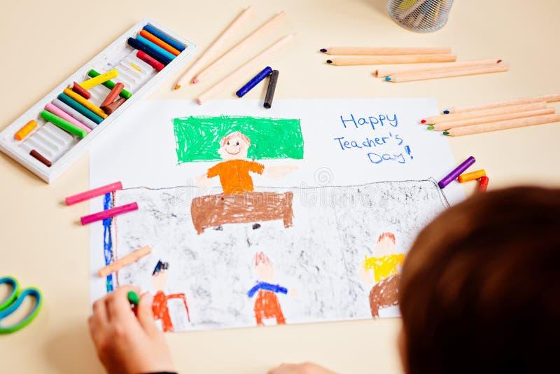 Il bambino disegna un disegno pastello del suo insegnante nella classe di scuola immagini stock libere da diritti
