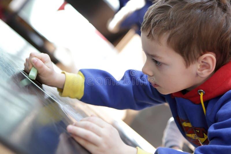 Il bambino disegna un gesso fotografia stock libera da diritti