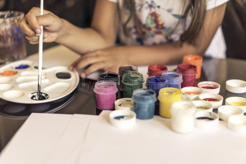 Il bambino disegna un'immagine di un acquerello e di una gouache su carta immagini stock libere da diritti