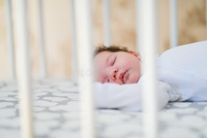 Il bambino dorme nella greppia Un bambino affascinante dorme in una greppia per il sonno allegato al letto dei genitori Un piccol fotografia stock libera da diritti