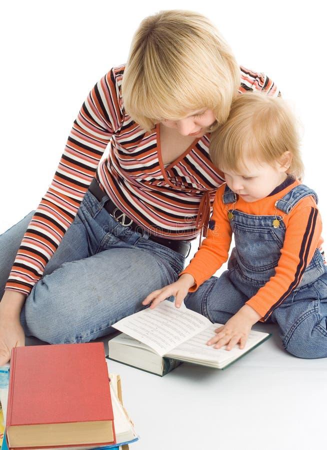 Il bambino e la madre graziosi hanno letto i libri immagini stock libere da diritti