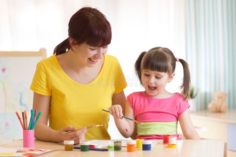 Il bambino e la mamma felici dipingono insieme La donna adulta aiuta la ragazza del bambino immagini stock libere da diritti