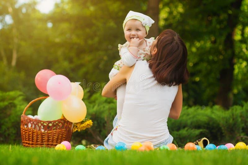 Il bambino e la mamma svegli stanno giocando sull'erba verde fotografia stock