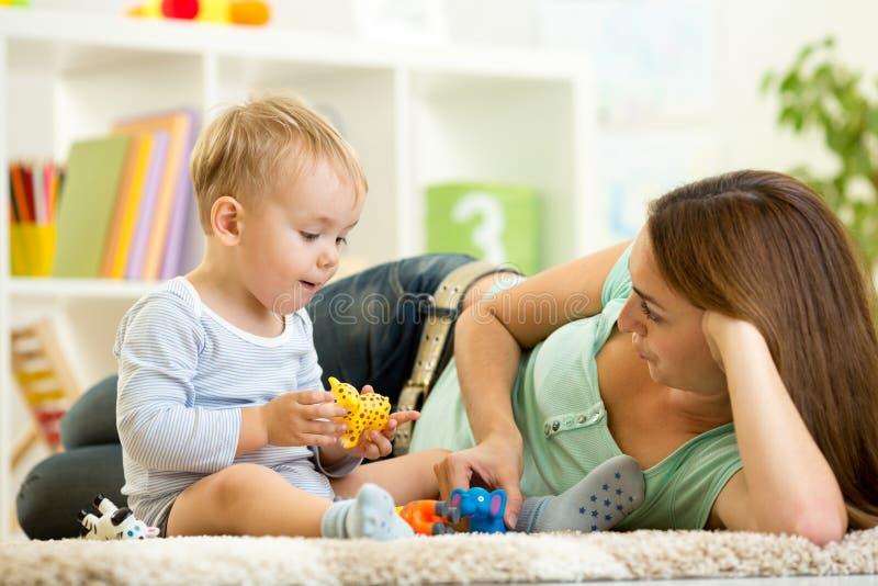 Il bambino e la sua mamma giocano i giocattoli dell'animale della tenuta dello zoo fotografia stock