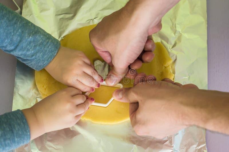 Il bambino ed il papà fa le taglierine del biscotto della pasta immagine stock libera da diritti