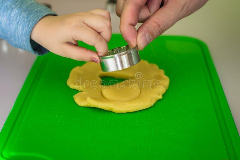 Il bambino ed il papà fa le taglierine del biscotto della pasta fotografia stock