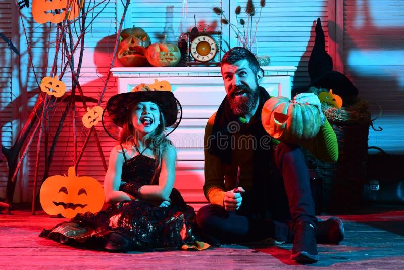 Il bambino ed il padre scolpiscono la zucca per il partito di Halloween Bambino e padre agghindati per la festa in costume Hallow fotografie stock libere da diritti