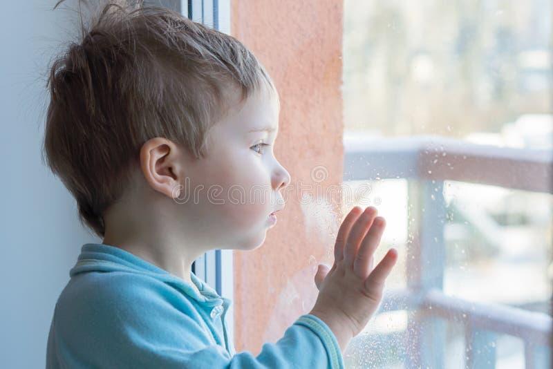 Il bambino esamina la finestra nella sorpresa fotografia stock libera da diritti