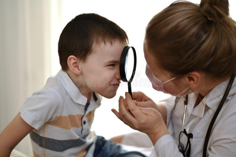 Il bambino esamina il medico attraverso il vetro fotografie stock