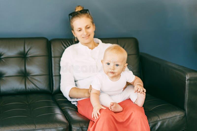 Il bambino esamina stranamente la macchina fotografica mentre si siede alle ginocchia della mamma immagini stock libere da diritti