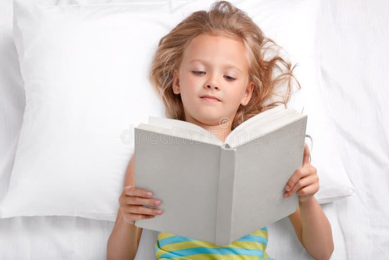 Il bambino in età prescolare abbastanza piccolo legge la storia attentamente interessante, tiene il libro aperto, si trova a lett immagine stock