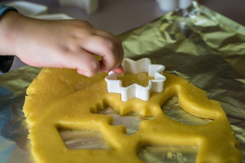 Il bambino fa le taglierine del biscotto della pasta immagini stock