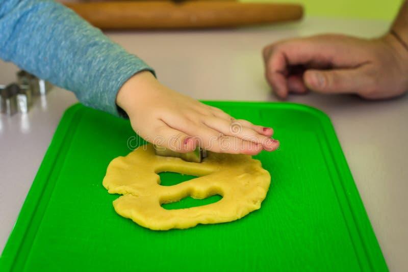 Il bambino fa le taglierine del biscotto della pasta fotografie stock