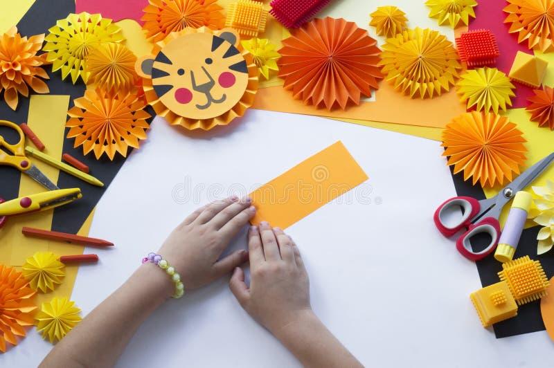 Il bambino fa una carta fatta a mano Origami della tigre fotografia stock
