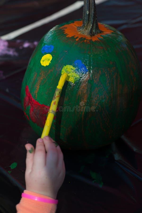 Il bambino felice al festival del raccolto, dipingente un fronte dei colori si inverdisce, giallo e rosso su una zucca fotografia stock