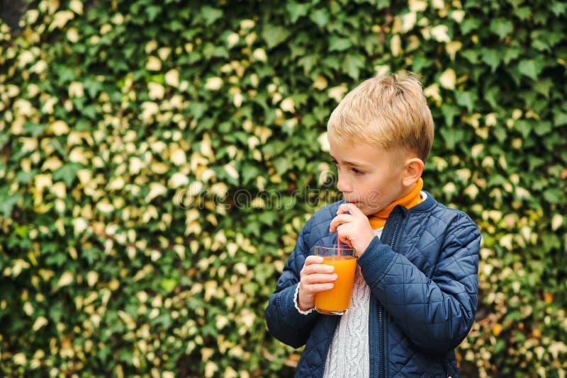 Il bambino felice beve il succo d'arancia all'aperto Concetto sano dell'alimento Succo di frutta fresca per i bambini Stile di vi fotografia stock libera da diritti