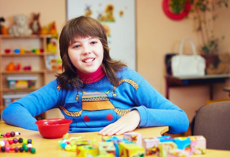 Il bambino felice con l'inabilità sviluppa le capacità motorie fini al centro di riabilitazione per i bambini con i bisogni speci fotografia stock libera da diritti