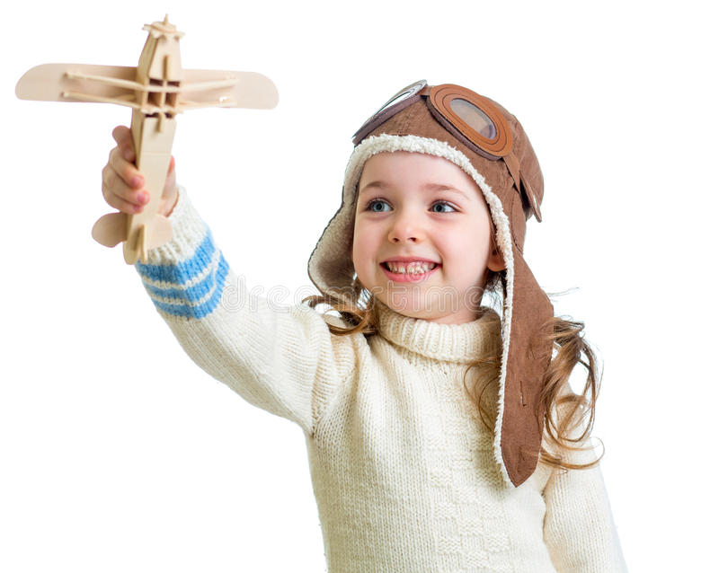 Il bambino felice ha vestito il pilota ed il gioco con il giocattolo di legno dell'aeroplano fotografia stock