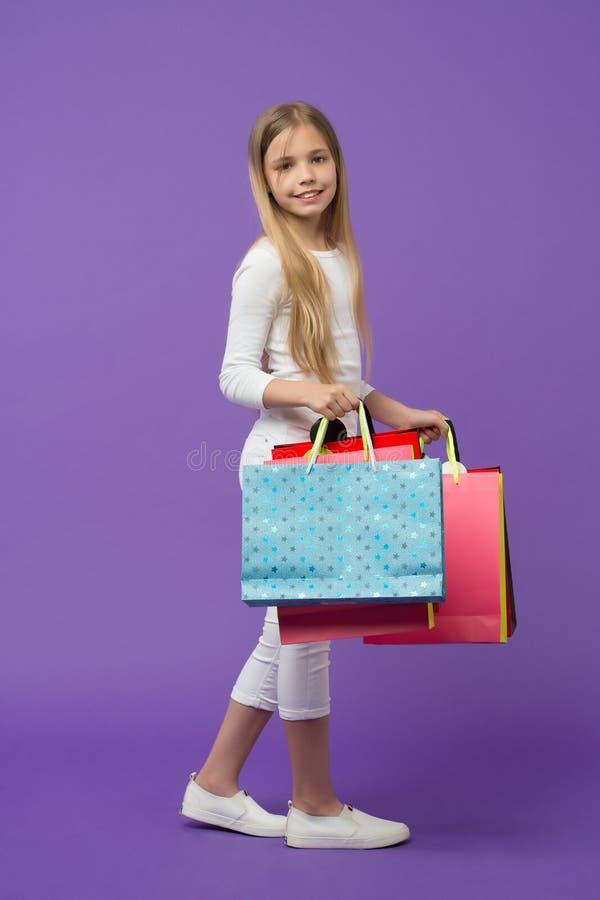 Il bambino felice porta i sacchetti della spesa su fondo viola Piccolo sorriso shopaholic con i sacchi di carta Cliente della rag fotografia stock libera da diritti