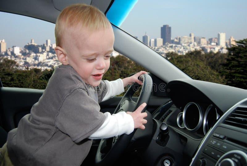 Il bambino finge di condurre l'automobile in grande città immagini stock