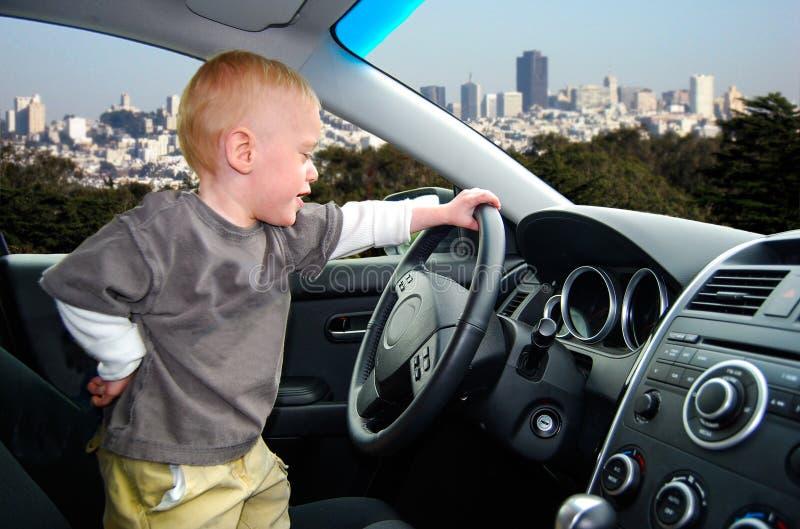 Il bambino finge di condurre l'automobile in grande città fotografie stock libere da diritti