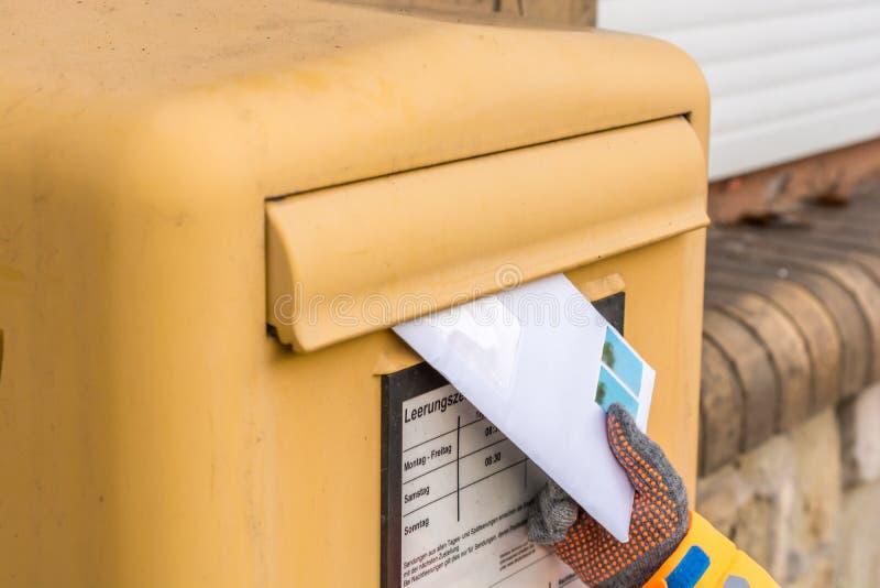 Il bambino getta una lettera nella cassetta delle lettere immagine stock libera da diritti