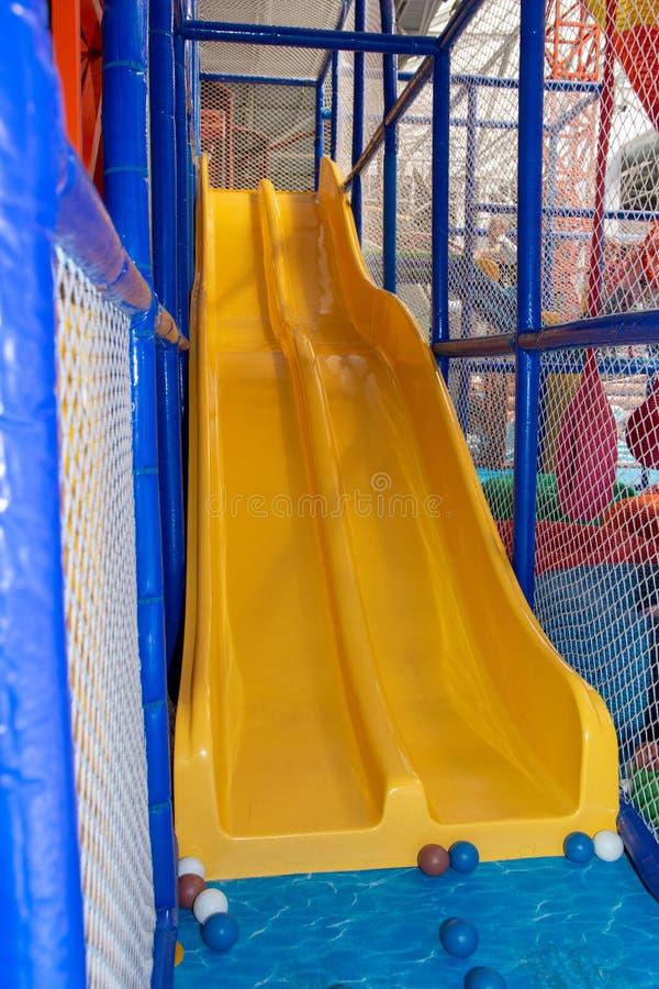 Il bambino gioca felicemente sul campo da giuoco immagine stock libera da diritti