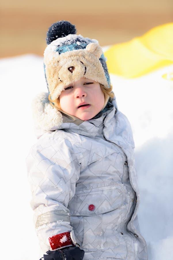 Il bambino gioca nella neve dell'inverno immagine stock