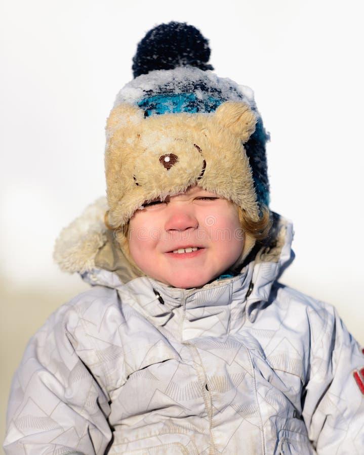 Il bambino gioca nella neve dell'inverno fotografia stock