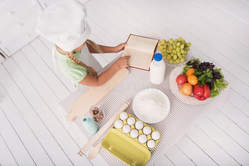 Il bambino grazioso vuole cucinare qualche cosa di delizioso immagini stock libere da diritti
