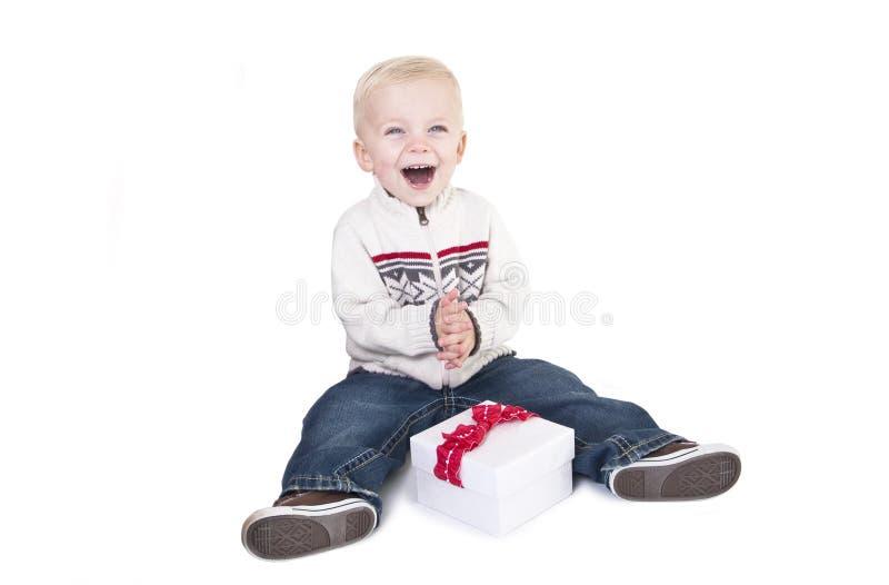Il bambino ha eccitato circa l'apertura del suo presente nuovo immagine stock libera da diritti