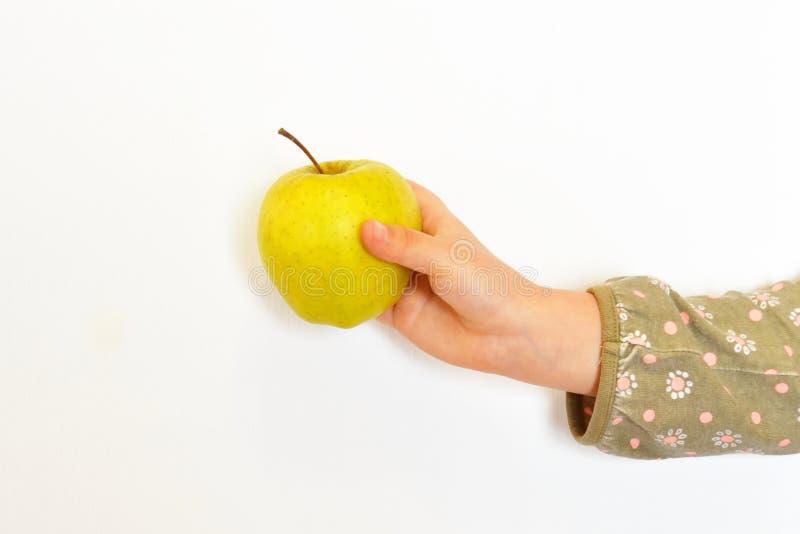 Il bambino ha preso una mela in sua mano Il piccolo bambino tiene una mela in sua mano La mano dei bambini con la mela su fondo b fotografia stock