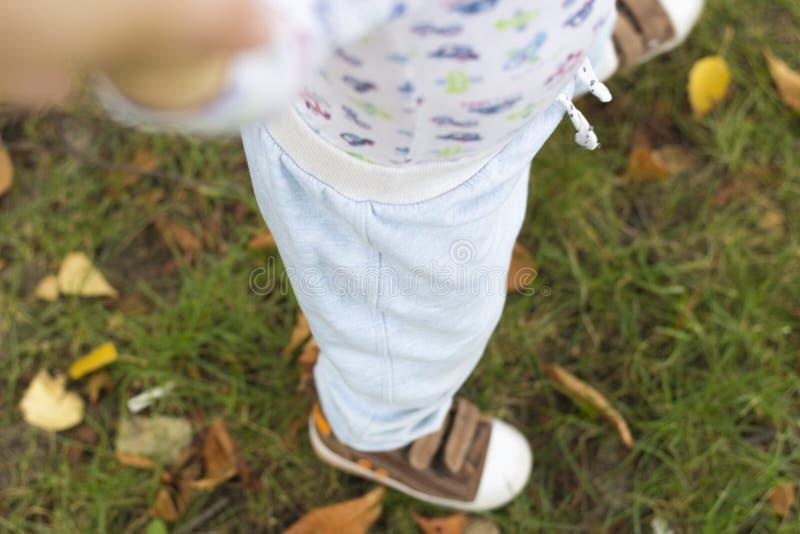 Il bambino impara camminare nel parco sull'erba, selfi del bambino immagini stock
