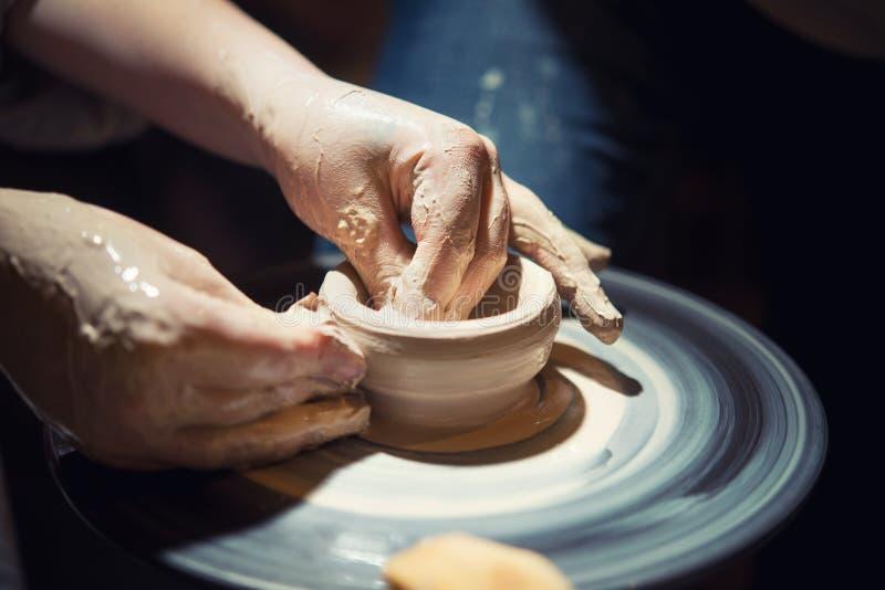Il bambino impara come scolpire un piatto ceramico fotografia stock