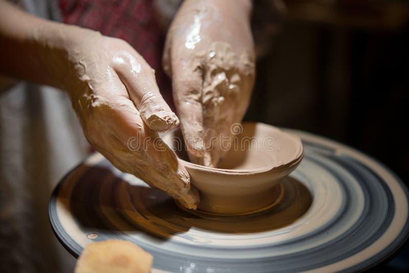 Il bambino impara come scolpire un piatto ceramico immagine stock
