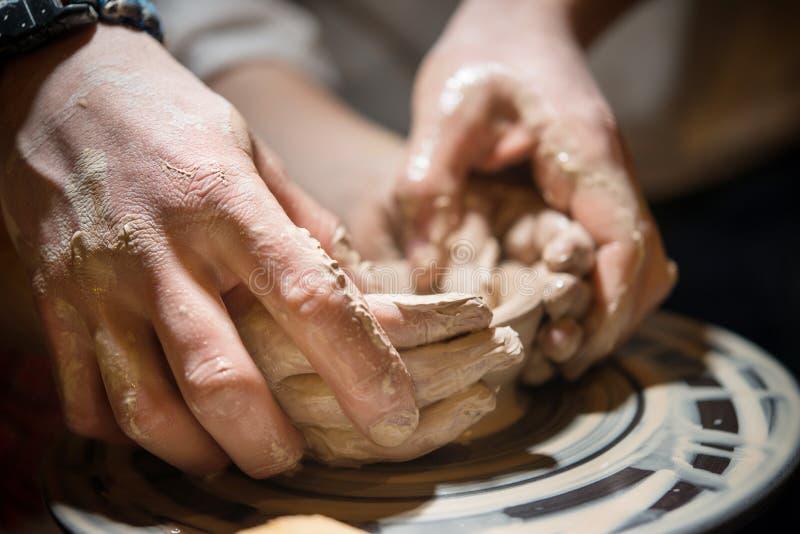Il bambino impara fare le terraglie sulla ruota del ` s del vasaio immagine stock