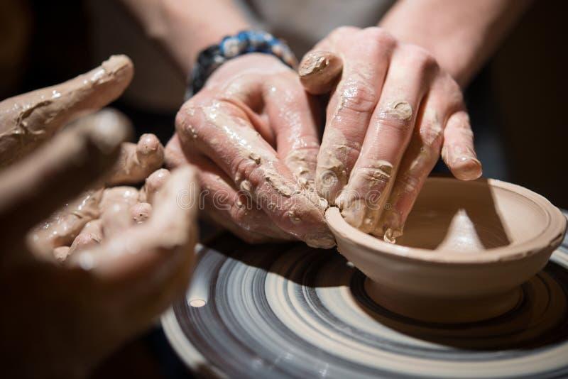 Il bambino impara fare le terraglie sulla ruota del ` s del vasaio fotografie stock libere da diritti