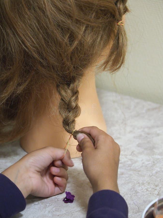 Il bambino impara fare le trecce su un manichino fotografia stock libera da diritti