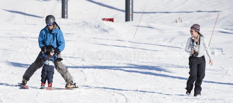 Il bambino impara sciare con il papà mentre gli orologi & la mamma prende le foto fotografia stock libera da diritti