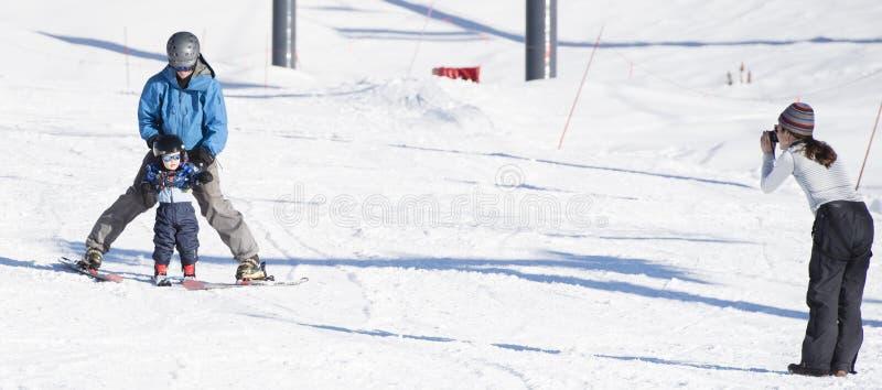Il bambino impara sciare con il papà mentre la mamma prende una foto immagini stock libere da diritti