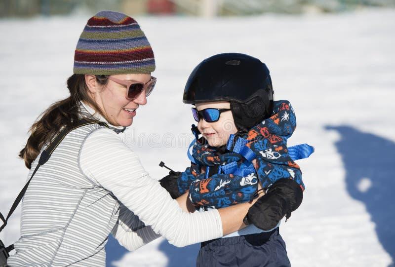 Il bambino impara sciare con la mamma Vestito sicuro con il casco immagine stock