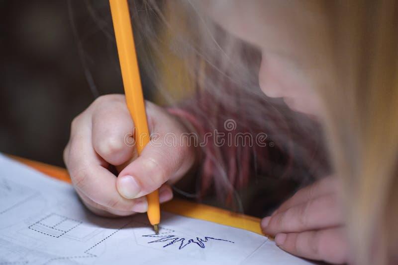 Il bambino impara scrivere e disegna una penna intorno alla linea di contorno fotografia stock libera da diritti