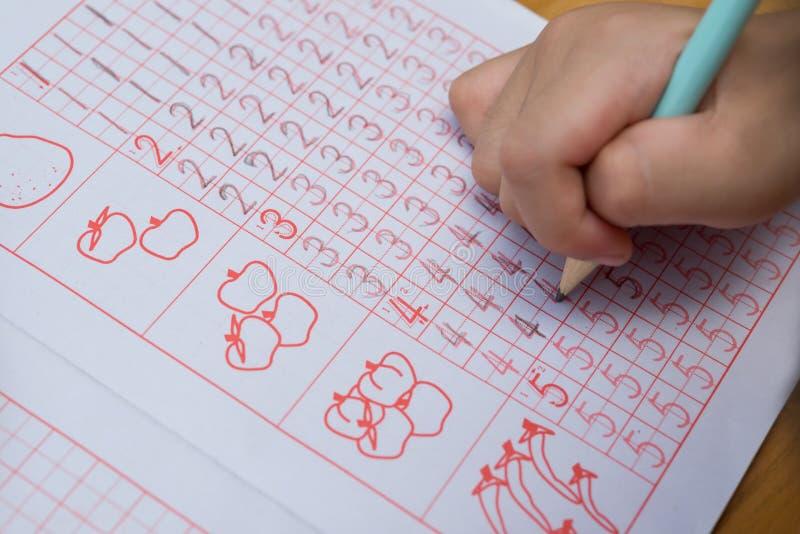 Il bambino impara scrivere i numeri arabi dalla seguente guida immagine stock