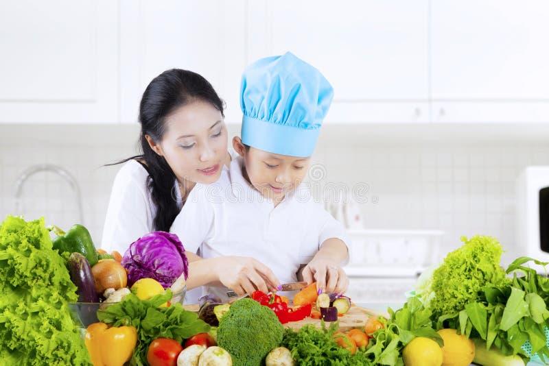 Il bambino impara tagliare le verdure in cucina immagini stock libere da diritti