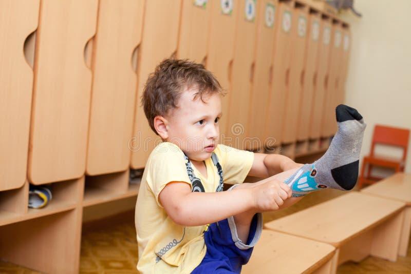 Il bambino indossa i calzini nell'asilo fotografie stock libere da diritti
