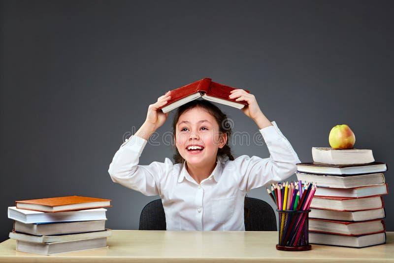 Il bambino industrioso sveglio sta sedendosi ad uno scrittorio all'interno Il bambino sta imparando nella classe su fondo della l immagine stock libera da diritti