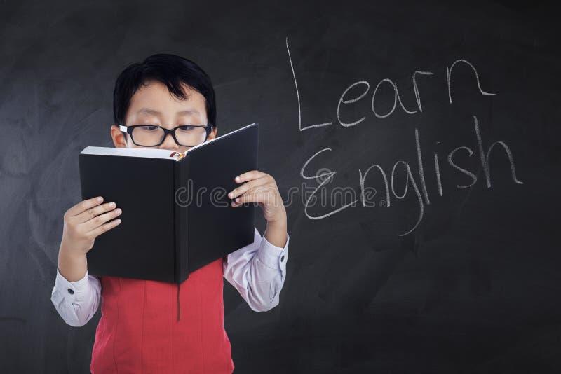 Il bambino legge il libro con testo impara l'inglese immagini stock