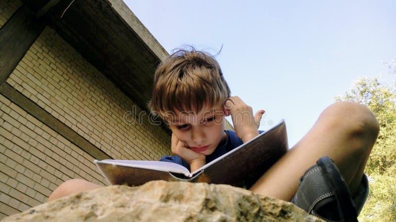 Il bambino legge un libro che si siede su una pietra e che graffia la sua testa fotografia stock libera da diritti